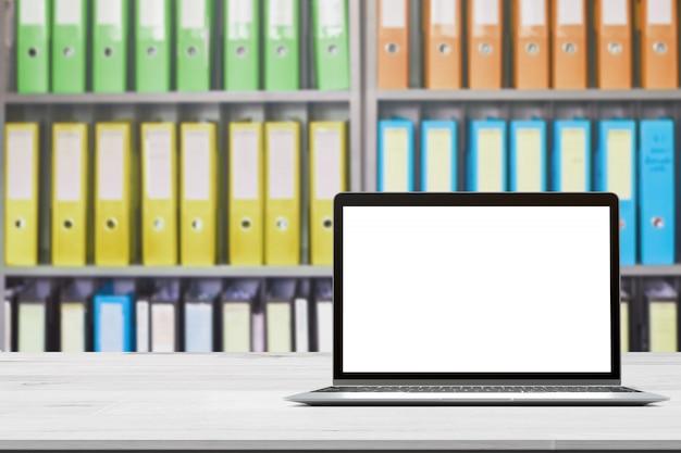 Plateau en bois avec ordinateur portable sur dossiers de documents de bureau flou debout dans une rangée de sur le stockage de documents pour le fond Photo Premium