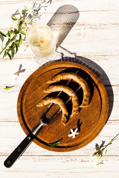 Plateau en bois avec des saucisses grillées sur une fourchette Photo gratuit