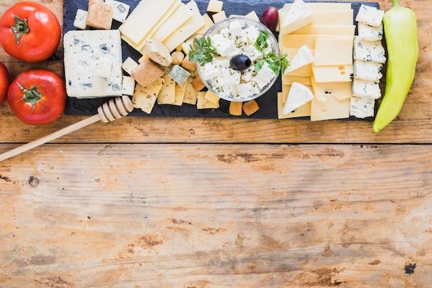 Plateau de fromages servi avec tomates rouges et poivrons verts sur une table en bois Photo gratuit