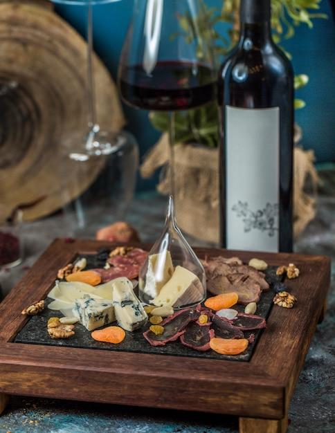 Plateau de fromages et un verre avec une bouteille de vin rouge Photo gratuit