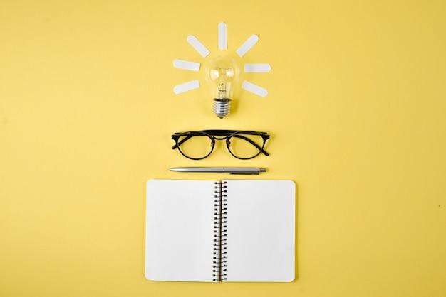 Plateau de planification financière avec stylo, bloc-notes, lunettes et ampoule sur fond jaune. Photo Premium