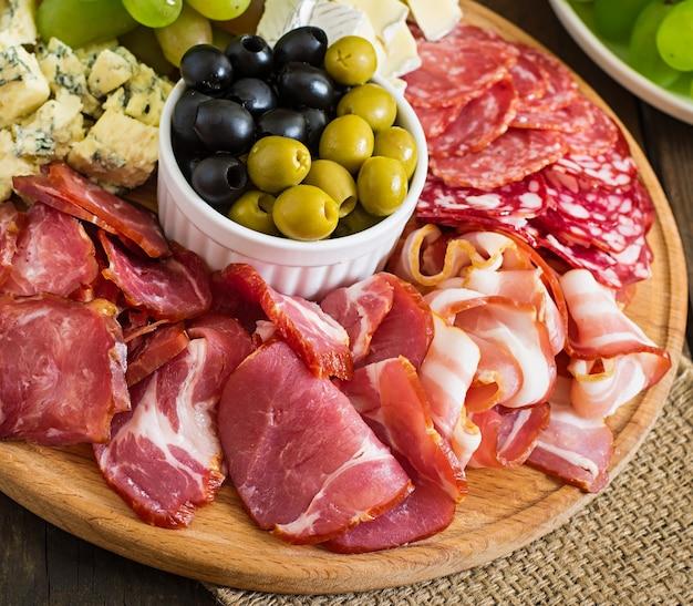 Plateau De Restauration Antipasto Avec Bacon, Saccadé, Salami, Fromage Et Raisins Sur Une Table En Bois Photo gratuit