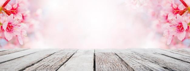 Plateau de table en bois vide et arbre fleuri floue de sakura sur fond de bannière de jardin Photo Premium