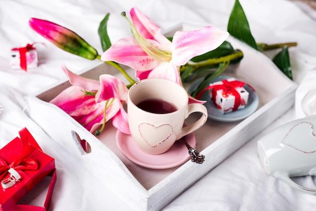 Plateau avec une tasse de thé chaud dans le lit Photo Premium