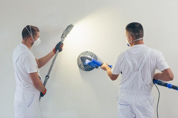 Le Plâtrier Lisse La Surface Du Mur Avec Une Machine Murale Avec Du Papier De Verre. Photo Premium