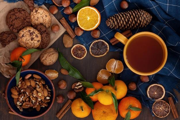 Plats d'hiver réconfortants - biscuits au chocolat, noix, mandarines et thé Photo Premium