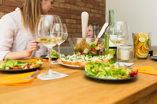 Plats de salade sur la table et la famille Photo gratuit