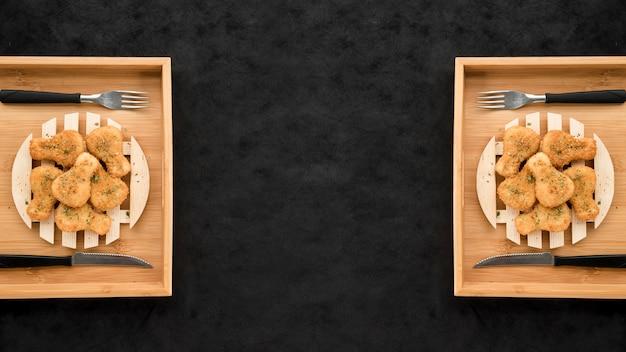 Plats servis de pépites de poulet sur le tableau noir grunge Photo gratuit