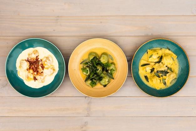 Plats vifs de pâtes aux raviolis disposées en rangées sur une table en bois Photo gratuit