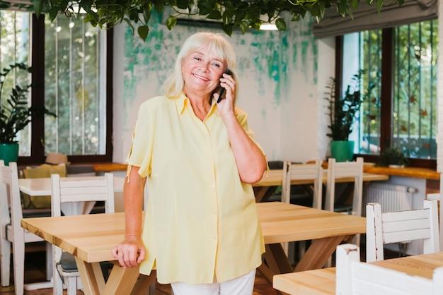 Pleasured Souriant Femme âgée Tenant Un Smartphone Près De L'oreille Photo gratuit