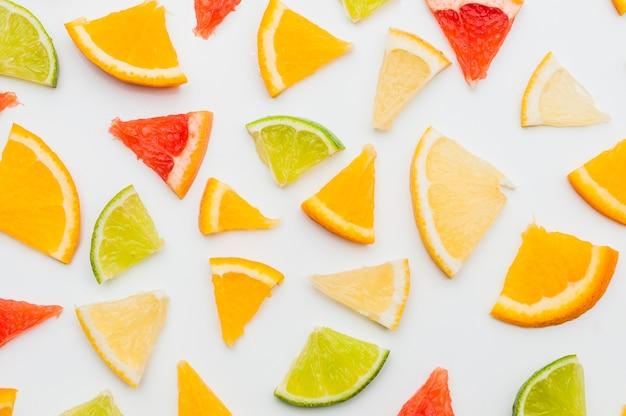 Plein cadre de tranches d'agrumes triangulaires sur fond blanc Photo gratuit