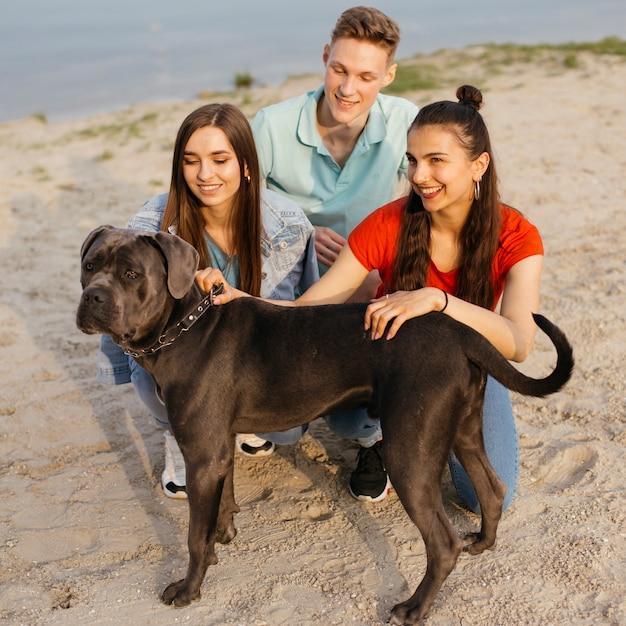 Plein coup des amis heureux avec chien mignon Photo gratuit