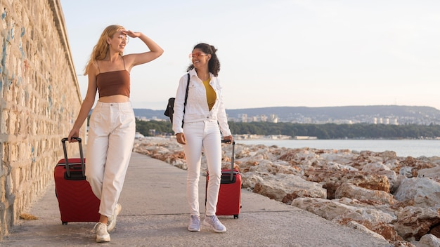 Plein Coup De Femmes Heureuses Transportant Des Bagages Photo gratuit