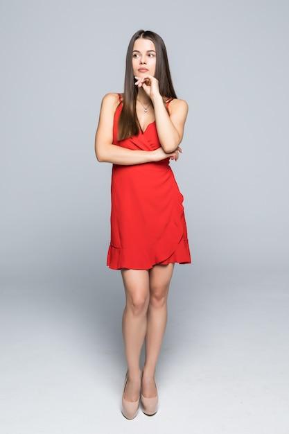 Pleine Hauteur De Jolie Femme De Mode Vêtue D'une Mince Robe Rouge Marchant Sur Le Mur. Photo gratuit