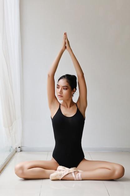 Pleine longueur attrayante jeune femme asiatique en robe de ballet exercer et assis dans une pose de yoga tout en se reposant à la maison Photo Premium