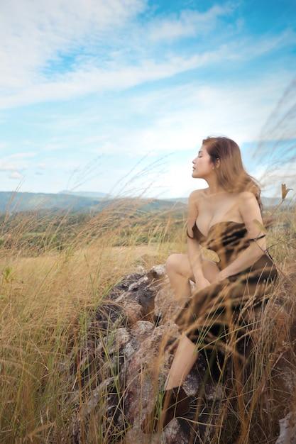 Pleine longueur jeune belle femme asiatique, cheveux longs en robe noire, assis dans la nature en plein air Photo Premium