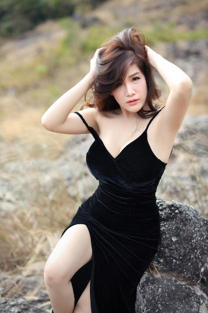 Pleine longueur jeune femme asiatique en robe noire assis dans la nature en plein air Photo Premium