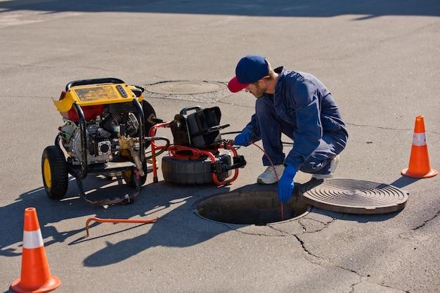 Un Plombier Diagnostique Un Puits De Drainage Dans La Rue à L'aide D'un équipement Spécial. Photo Premium