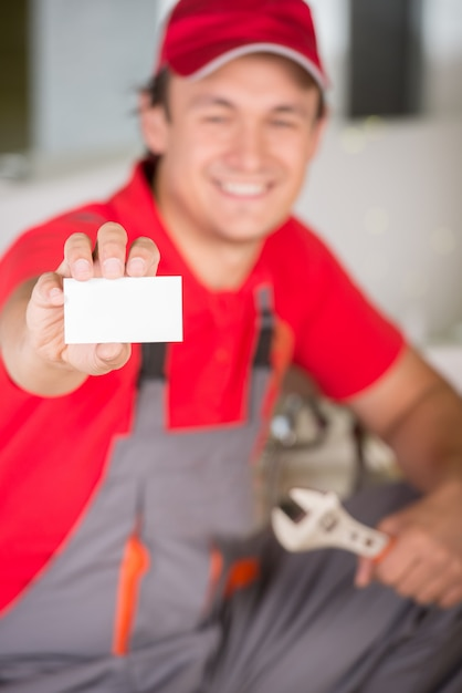 Plombier Tenant Une Clé Dans La Main Et Montrant La Carte De Visite. Photo Premium