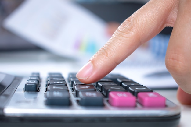 Plus près des mains des femmes, utilisez une calculatrice sur un bureau. vue de côté. Photo Premium