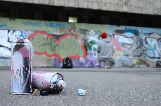 Plusieurs bombes aérosol de peinture rose et blanche se trouvent sur l'asphalte contre le mec debout Photo Premium
