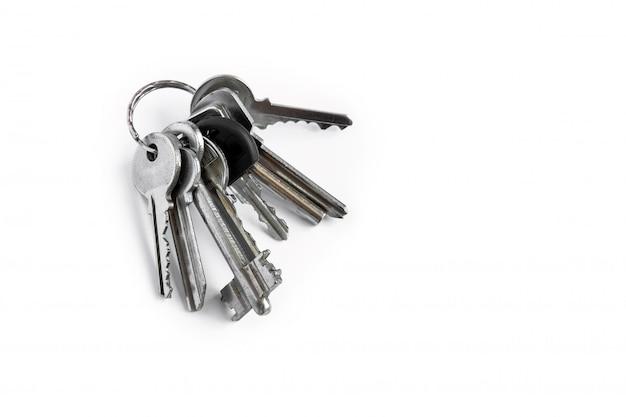 Plusieurs clés sur un fond blanc isolé, les clés de l'appartement. Photo Premium