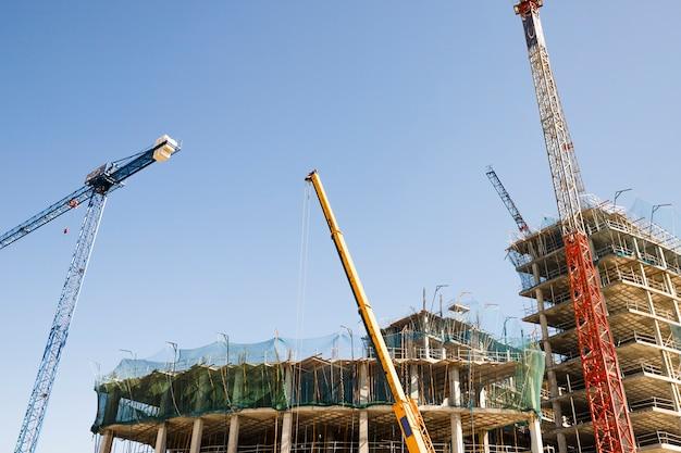 Plusieurs grues devant le bâtiment de construction contre le ciel bleu Photo gratuit