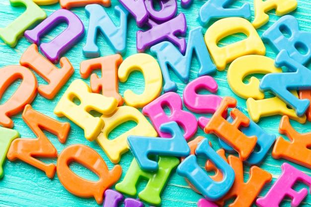 Plusieurs lettres colorées sur une table en bois Photo Premium