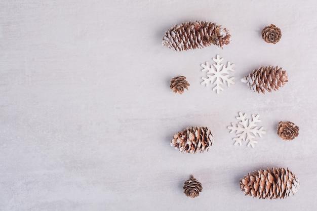 Plusieurs Pommes De Pin Et Flocons De Neige Sur Une Surface Blanche Photo gratuit