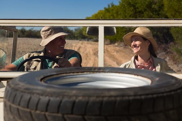 Pneu sur le capot avec un couple souriant assis dans un véhicule routier Photo gratuit