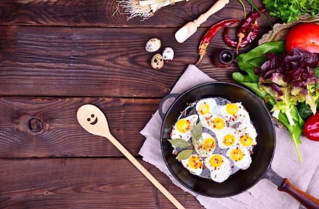 Poêle noire avec oeufs de caille frits Photo Premium