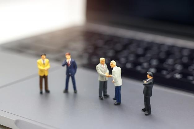Poignée d'homme d'affaires au succès de l'entreprise en ligne sur un ordinateur portable. Photo Premium