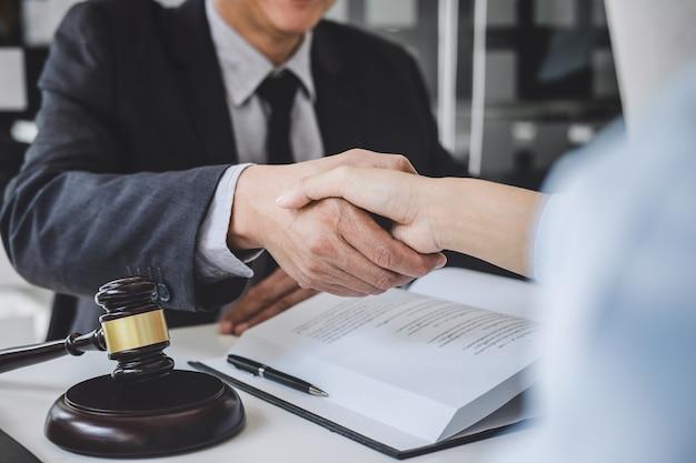 Poignée de main après une bonne coopération, femme d'affaires serrant la main d'un avocat professionnel après avoir discuté d'un bon contrat dans une salle d'audience, concepts de droit, juge martelé avec une balance de la justice Photo Premium