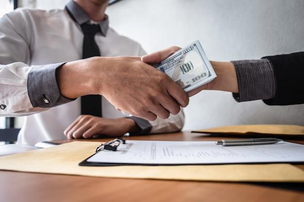 Poignée de main d'homme d'affaires avec de l'argent des billets en dollars en mains de tout donner un contrat de réussite Photo Premium