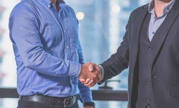 Poignée de main de partenariat de deux hommes d'affaires conviennent des affaires ensemble dans le bureau de travail Photo Premium