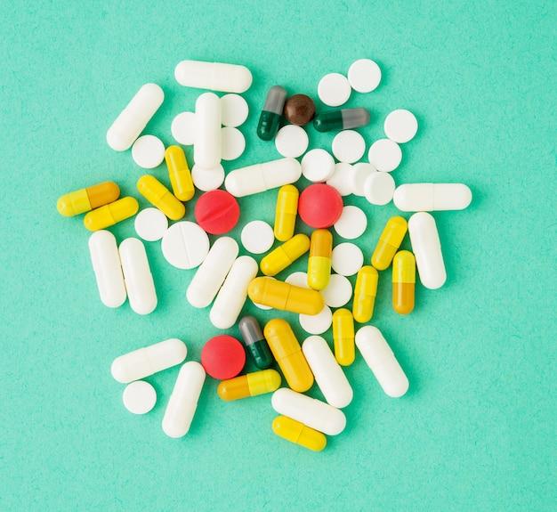 Poignée de médicaments dispersés, pilules et comprimés sur fond bleu Photo Premium