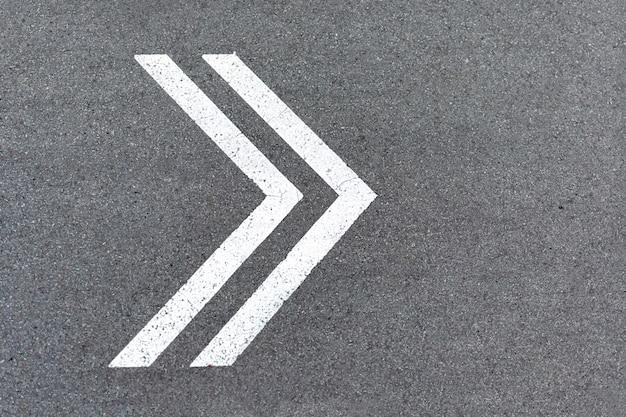 Le Pointeur De Flèche Est Dessiné Avec De La Peinture Blanche Sur La Route. Signe De Virage à Droite Sur L'asphalte, Sens Du Mouvement Photo Premium