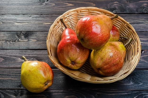 Poires rouge-jaune vif dans un panier sur un fond rustique en bois foncé. récolte d'automne de fruits. Photo Premium
