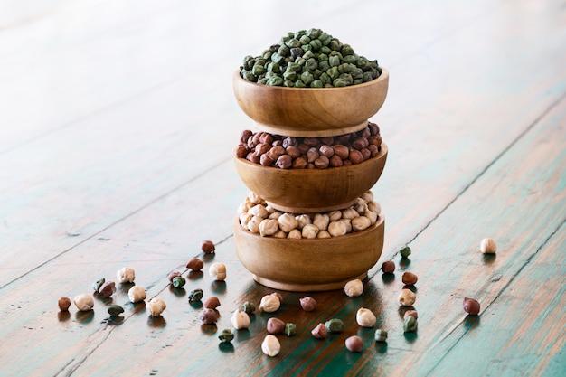 Pois chiches colorés (rouge, vert, blanc) dans des bols en bois sur fond rustique. Photo Premium
