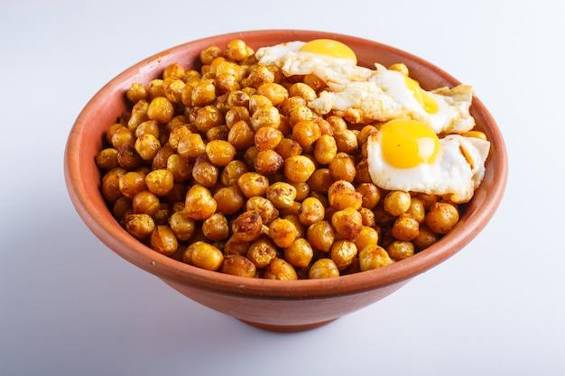 Pois Chiches Frits Avec Des œufs De Caille Et Des épices Dans Une Assiette En Argile Isolé Sur Fond Blanc Photo Premium