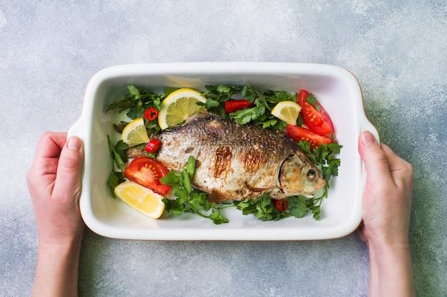 Poisson carpe cuit au four avec des légumes et des épices dans une plaque à pâtisserie avec espace pour copie. Photo Premium