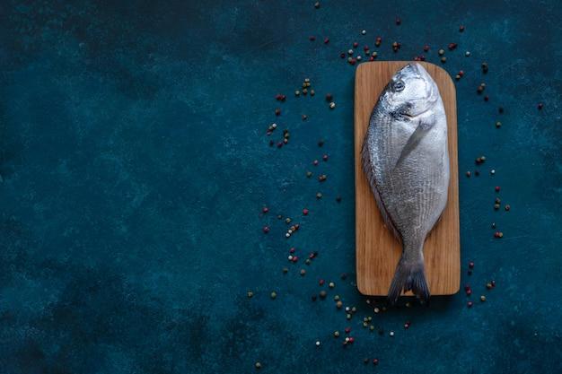 Poisson Dorado Frais Sur Une Planche à Découper En Bois Sur Une Table Bleue Photo Premium