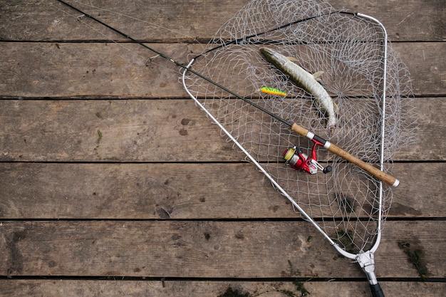 Poisson fraîchement pêché à l'intérieur du filet de pêche avec une canne à pêche sur la jetée en bois Photo gratuit