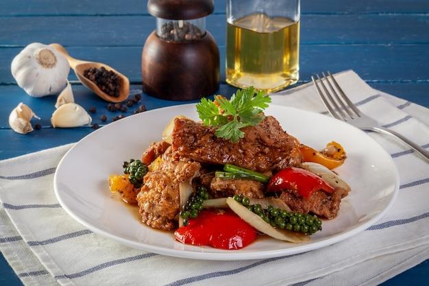 Poisson frit avec des légumes à la sauce au poivre noir Photo Premium