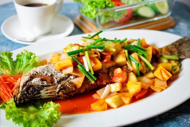Poisson frit à la mangue sur une table bleue avec une tasse de café blanche et des légumes Photo Premium