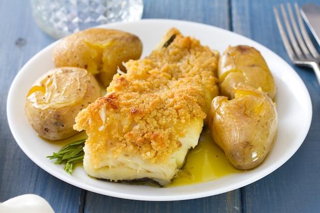 Poisson frit avec pomme de terre et huile sur plat et verre de vin Photo Premium