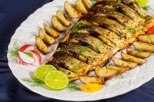Poisson grillé au four avec pommes de terre rôties et légumes Photo Premium