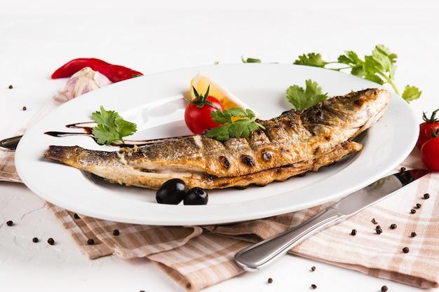 Poisson Grillé Aux Légumes Sur Une Plaque Blanche Photo Premium