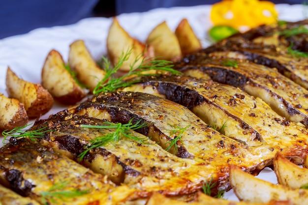 Poisson grillé avec pommes de terre rôties et légumes dans l'assiette Photo Premium