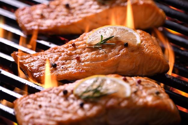 Poisson de saumon grillé avec divers légumes sur le gril enflammé Photo Premium